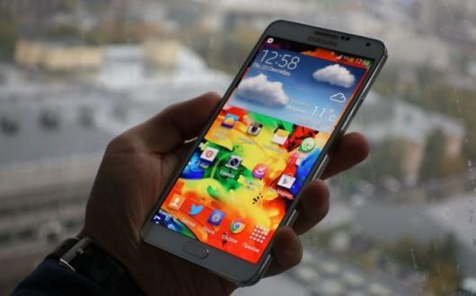 Samsung Galaxy Note III в руке на фоне окна