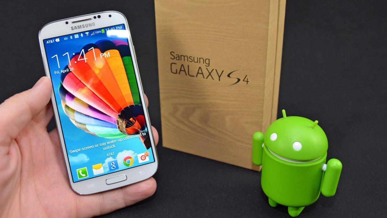 Телефон Samsung Galaxy s4 в мужской руке на фоне логотипа Android