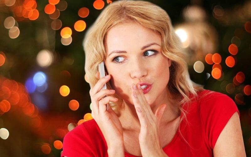 Девушка в красном говорит по мобильному на фоне праздничных огней города