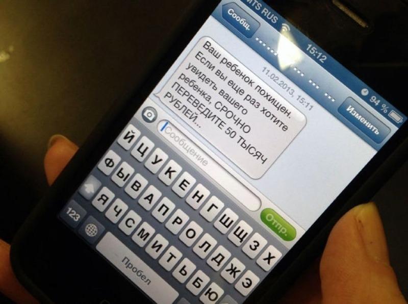 Телефон с сообщением о выкупе ребенка в руке